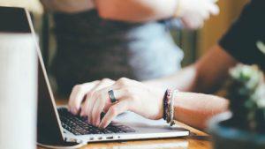 handen werken op laptop op bureau